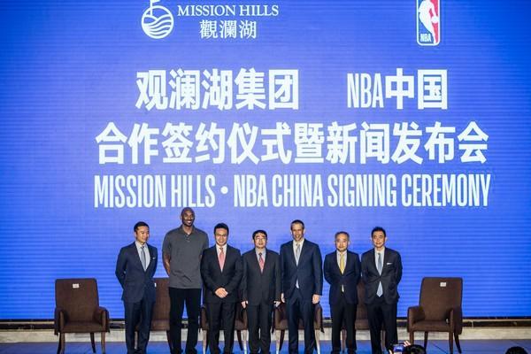 """虽然已经退役,但NBA巨星科比的人气依旧不减。这几天,这位前湖人的功勋球员正在进行中国行。昨天,他现身海口,亲自见证了观澜湖集团与NBA达成战略合作伙伴关系。 观澜湖与NBA的合作以篮球为中心,双方将在海口设计、建设和运营NBA篮球训练中心。据悉,海口观澜湖NBA篮球训练中心将面向从入门级到职业不同水准的男女青少年球员开放。训练中心将于今年开工,计划于2019年全面投入使用。 建成之后,NBA中国将负责运营工作,NBA现役和退役球员也将到访培训中心,为青少年球员提供训练指导。 此外,观澜湖高尔夫会将成为2017年NBA中国赛的官方推广合作伙伴。今年的中国赛将由金州勇士对阵明尼苏达森林狼。两队将于10月5日在深圳龙岗大运中心和10月8日在上海梅赛德斯-奔驰文化中心进行两场比赛。 观澜湖集团总部位于香港,是中国休闲产业的领航者,最早倡导发展休闲这个全新的朝阳产业,迄今已形成一个世界级的高尔夫和多元休闲产业群。观澜湖产业集群跨越深圳、东莞、海口三地,形成集运动、商务、养生、旅游、会议、文化、美食、购物、居住等为一体的国际休闲旅游度假区。其中以深圳、东莞为基地发展全球惟一汇聚五大洲风格的球会,以216洞规模被""""吉尼斯世界纪录组织""""认定为世界第一大高尔夫球会。 观澜湖集团主席为港区全国政协委员朱鼎健博士,以他的名字在企业查询宝中搜索,可以查到众多与观澜湖有关的企业都是他担任法人。目前,观澜湖集团在内地的总投资已经超过了400亿。"""