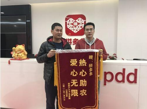 以果感恩店长张银杰(左)替新疆库尔勒梨农向拼多多送锦旗